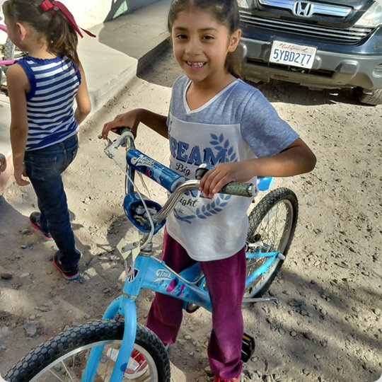 little girl on blue kids bike