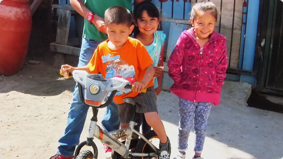 Three smiling kids with kids bike