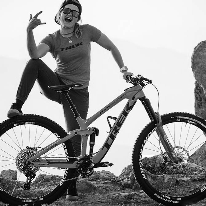 A woman poses with her mountain bike on rocks