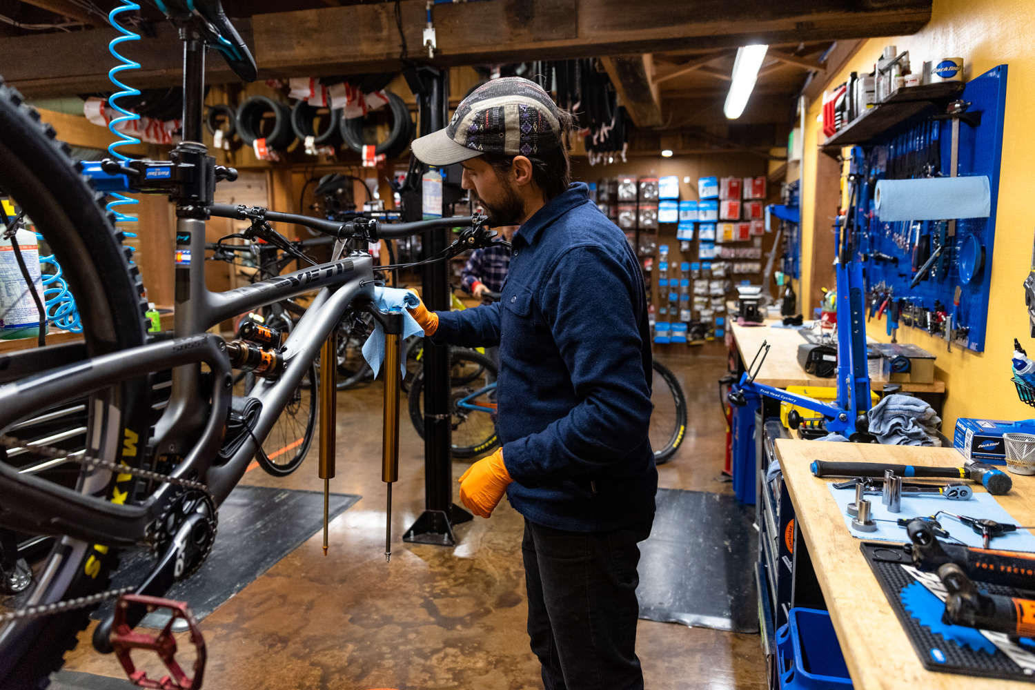 Bike mechanic servicing fork at trail head cyclery