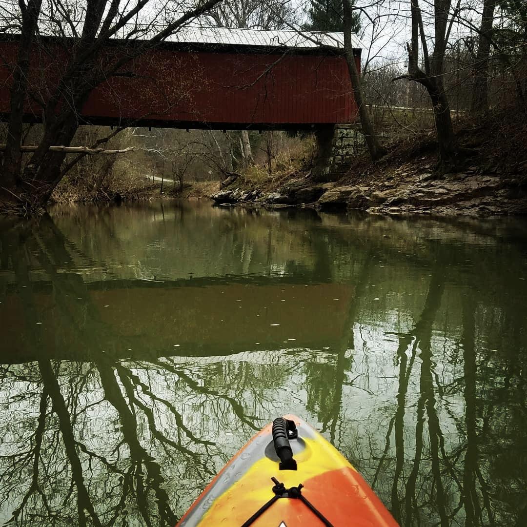Kayak on creek with covered bridge