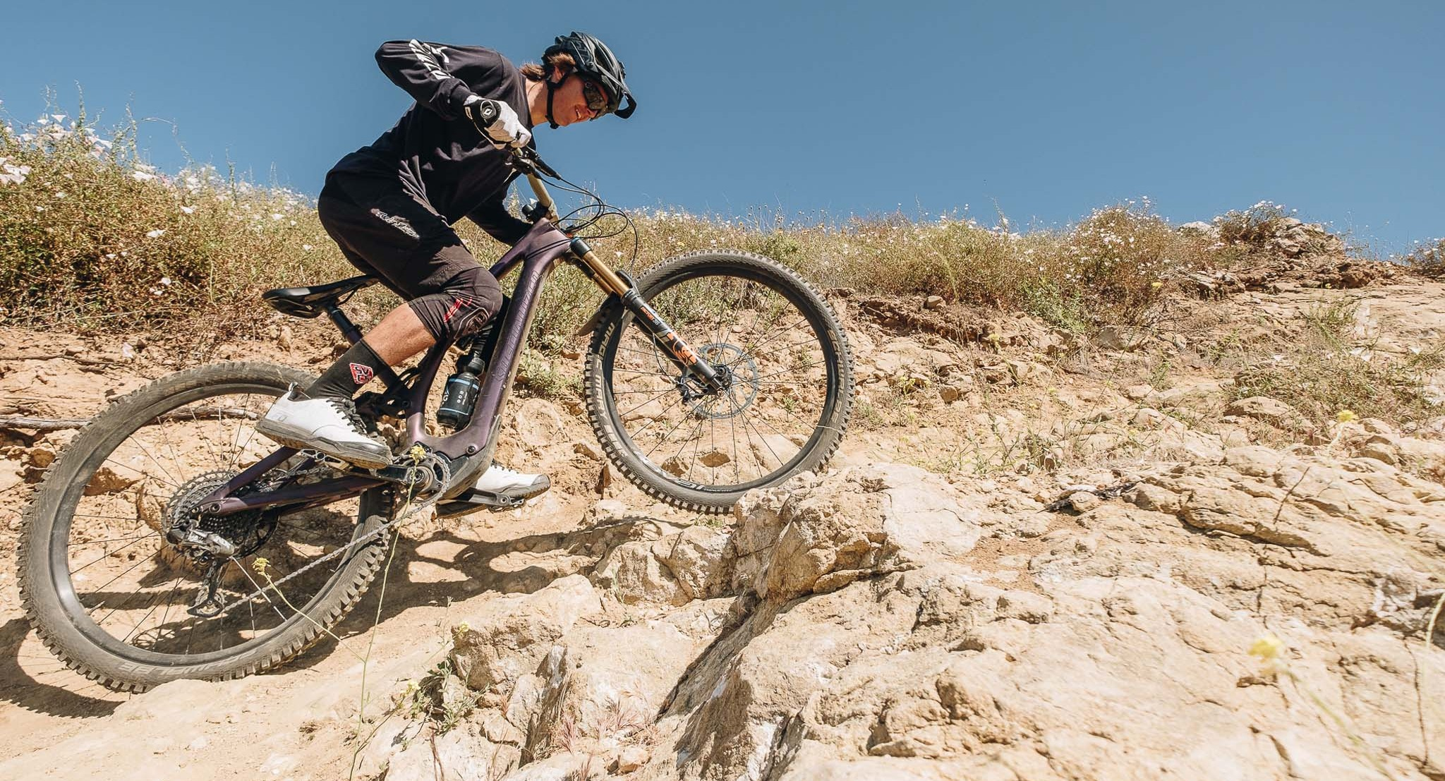 A mountain bike rides over rocks on a trail