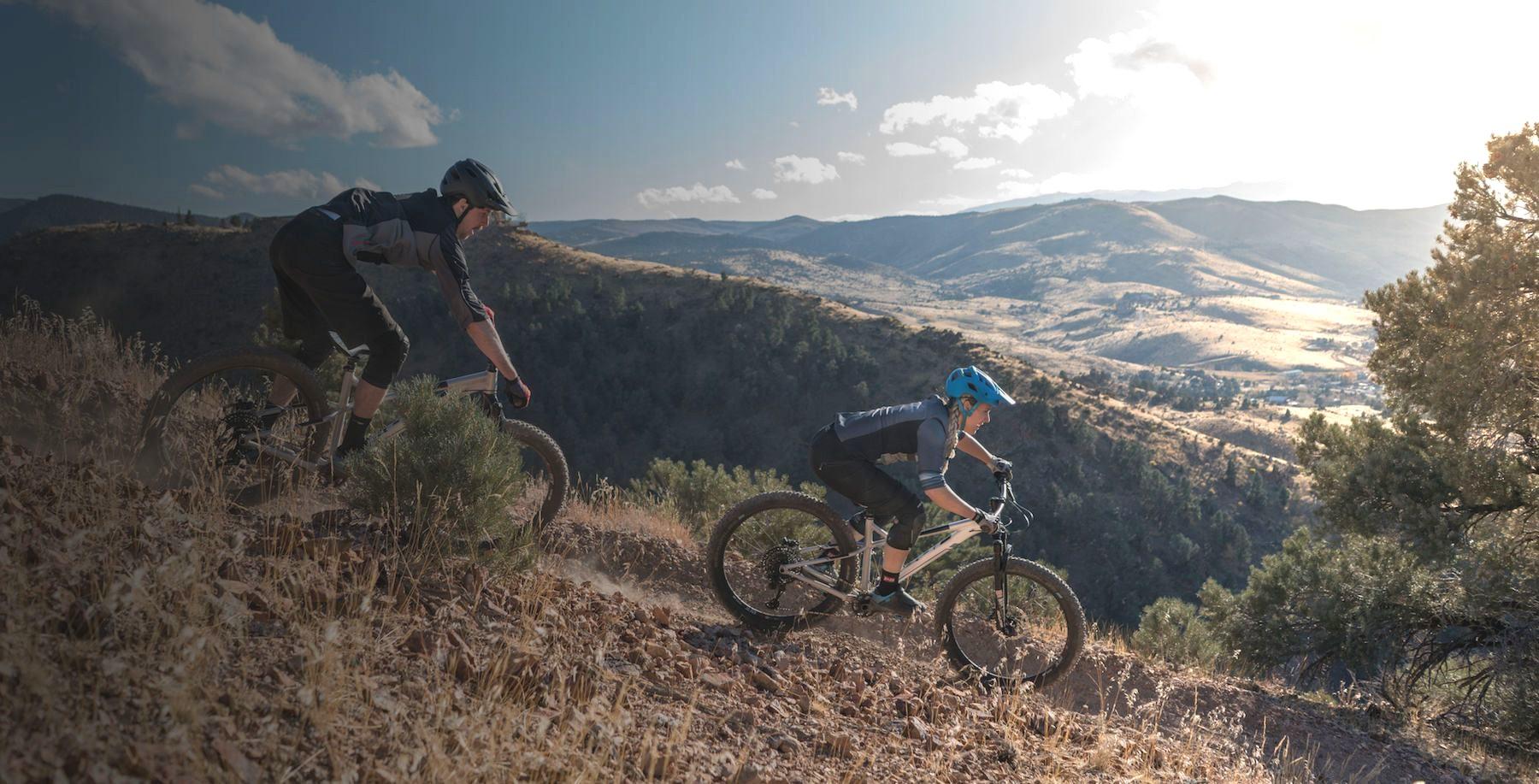 Two people mountain biking on Fuji bikes.