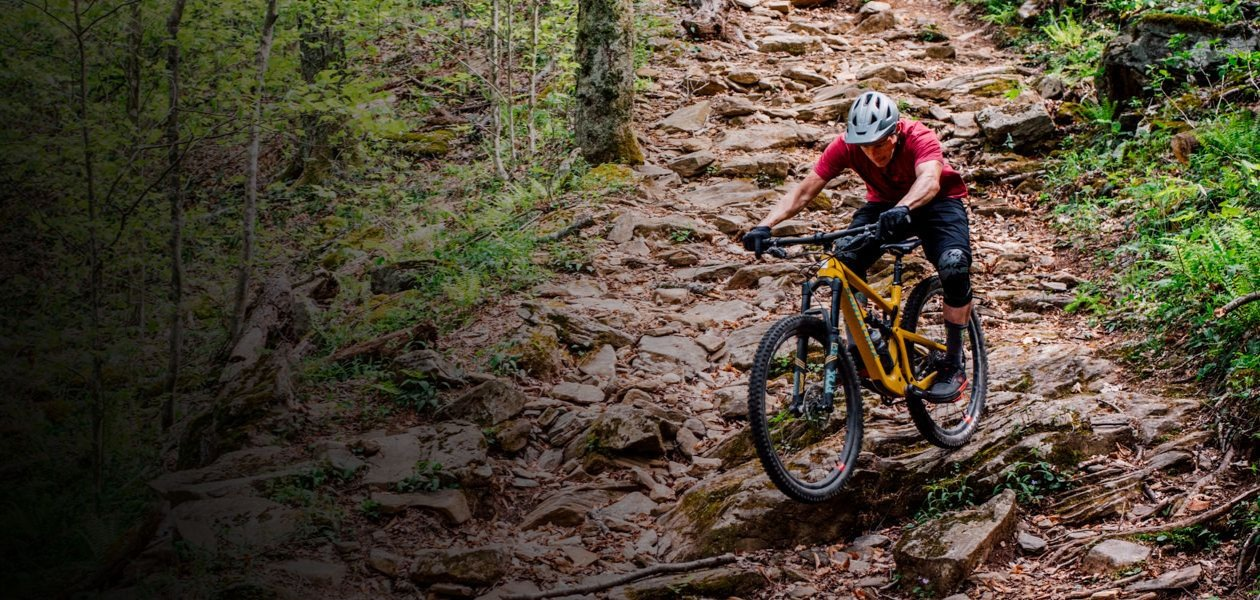 Mountain biker riding a Santa Cruz full-suspension bike.