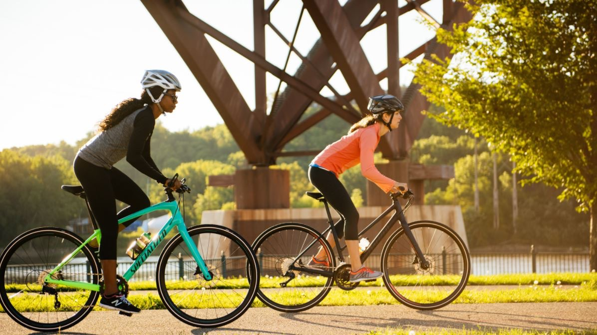 Two women riding hybrid bikes
