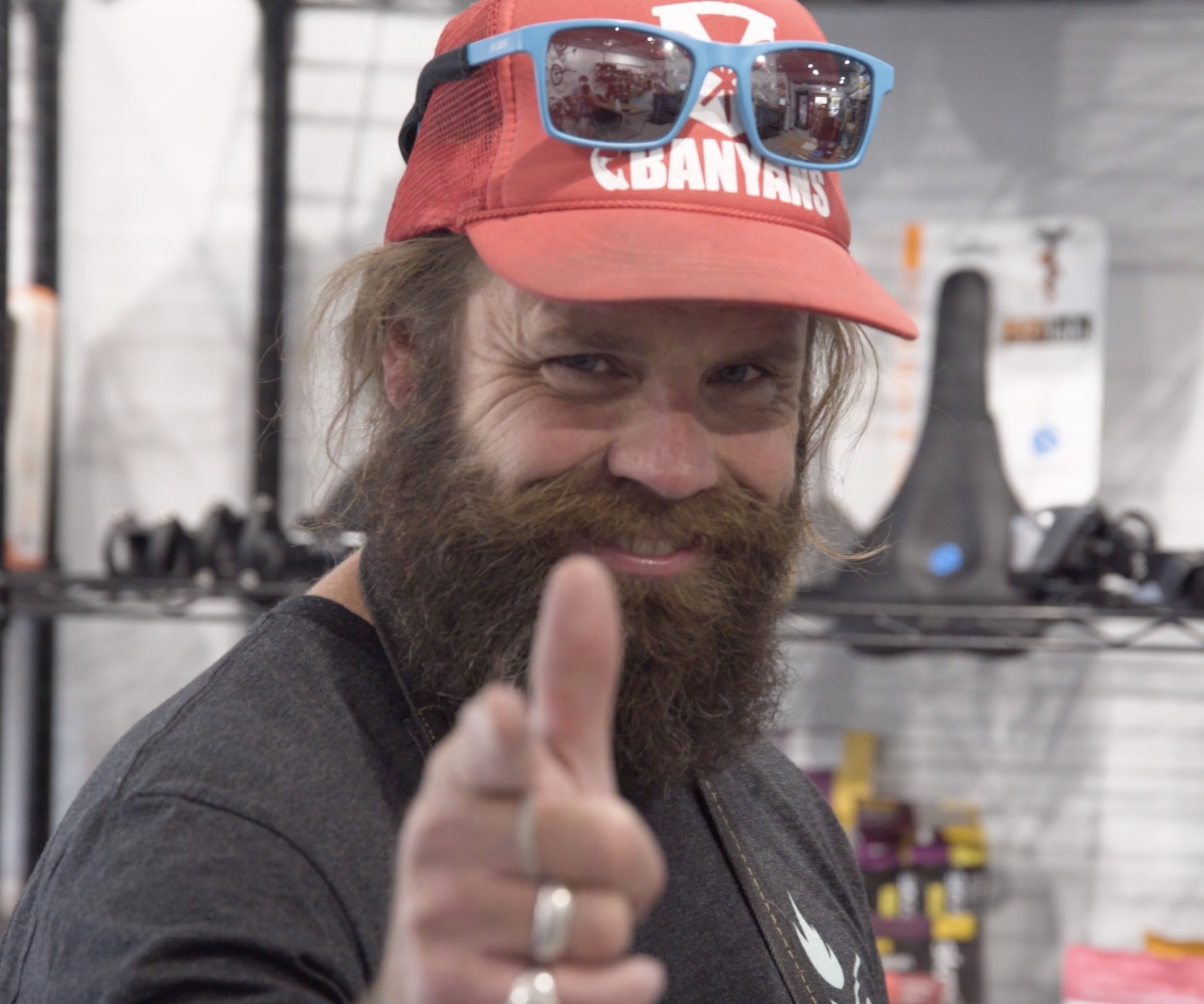 Smiling shop employee with a beard, hat and sunglasses.