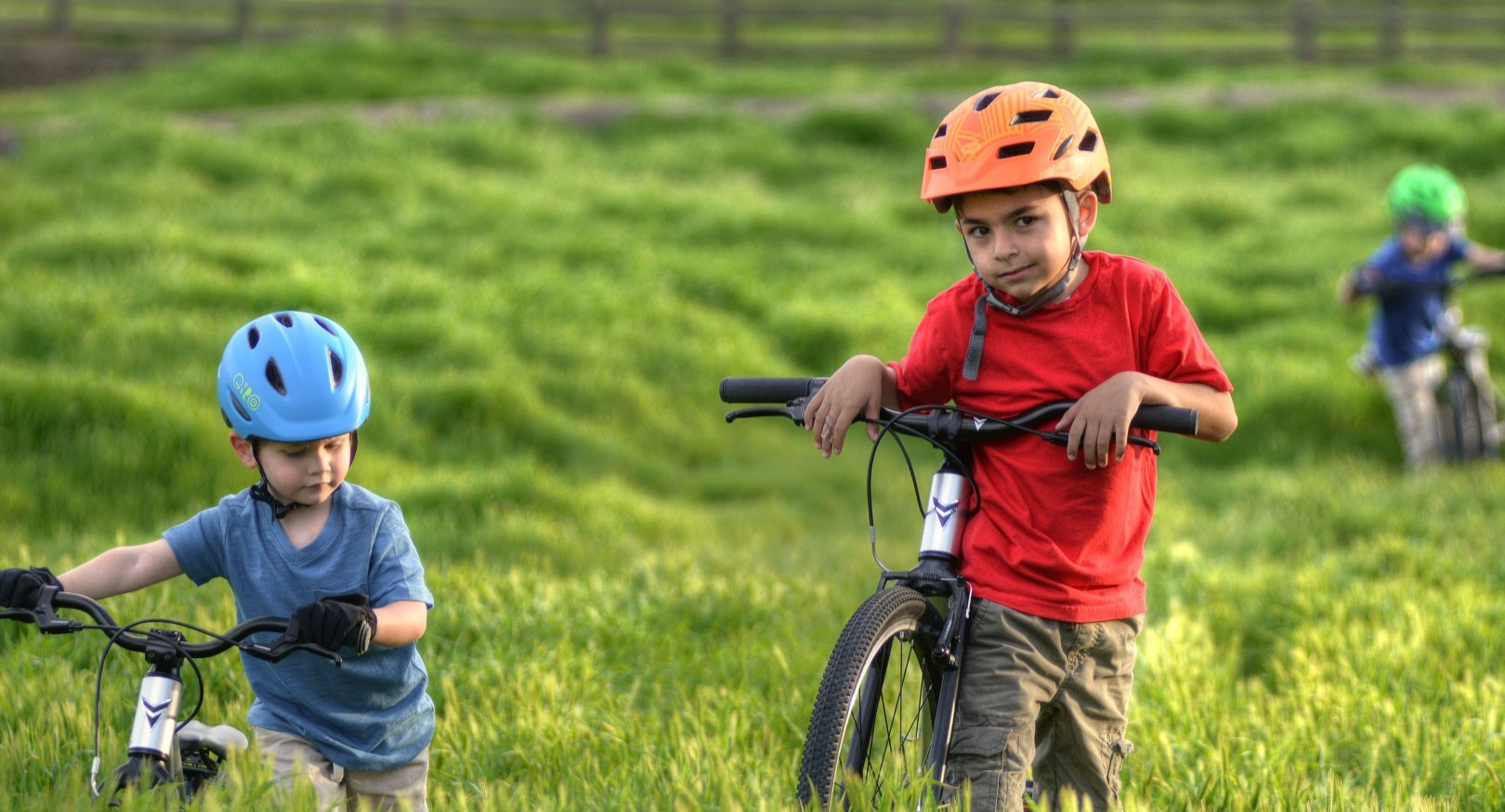 Two boys leaning on bikes in a long grass field.