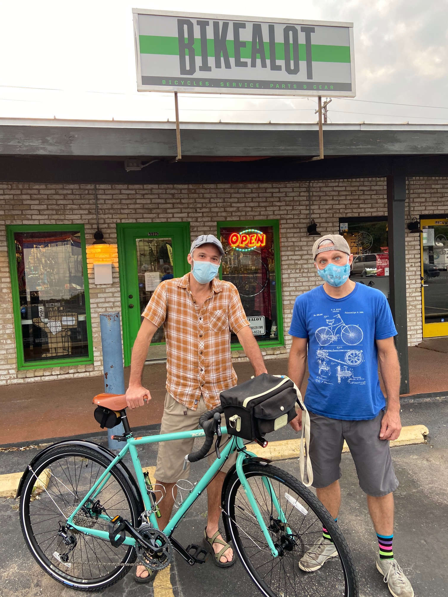 Both wearing masks, Brad and his brother, Shane, with Shane's new Kona Sutra, standing in front of the store