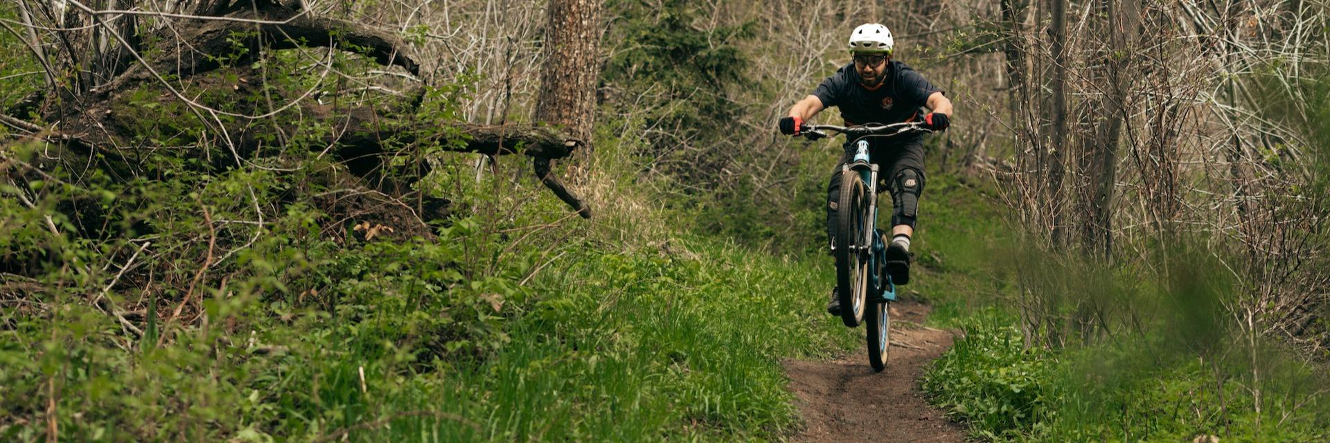 Man doing a wheelie on a mountain bike on a wooded trail