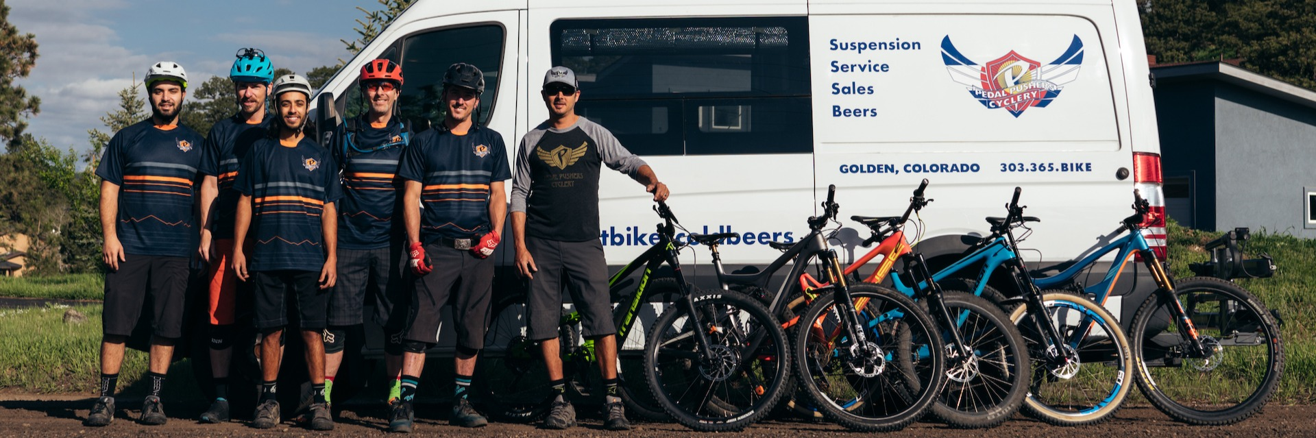6 men standing in front of white Pedal Pushers Cyclery van with mountain bikes