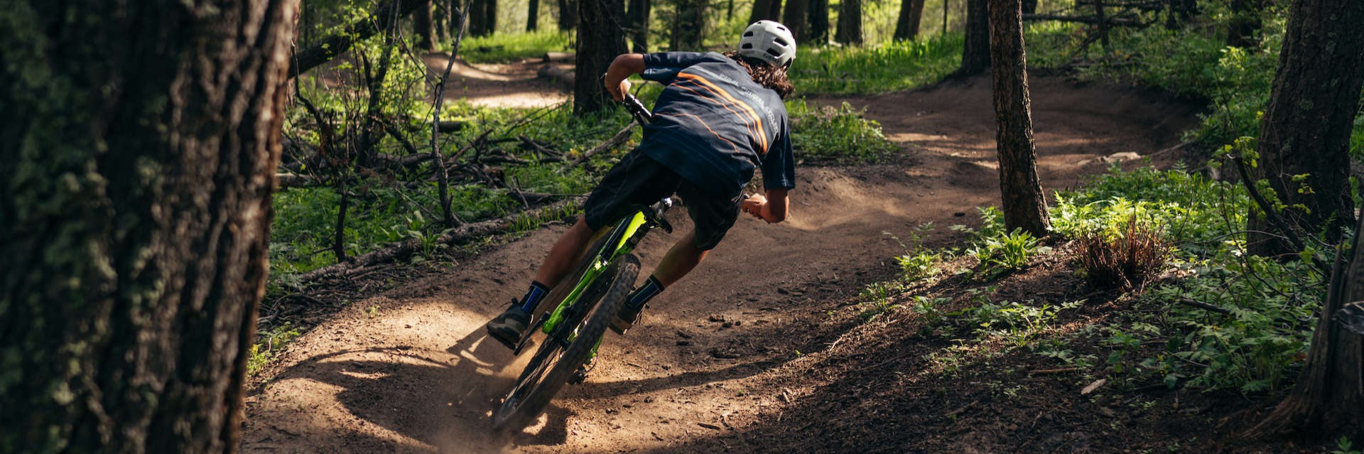 Man riding green mountain bike on a wooded trail