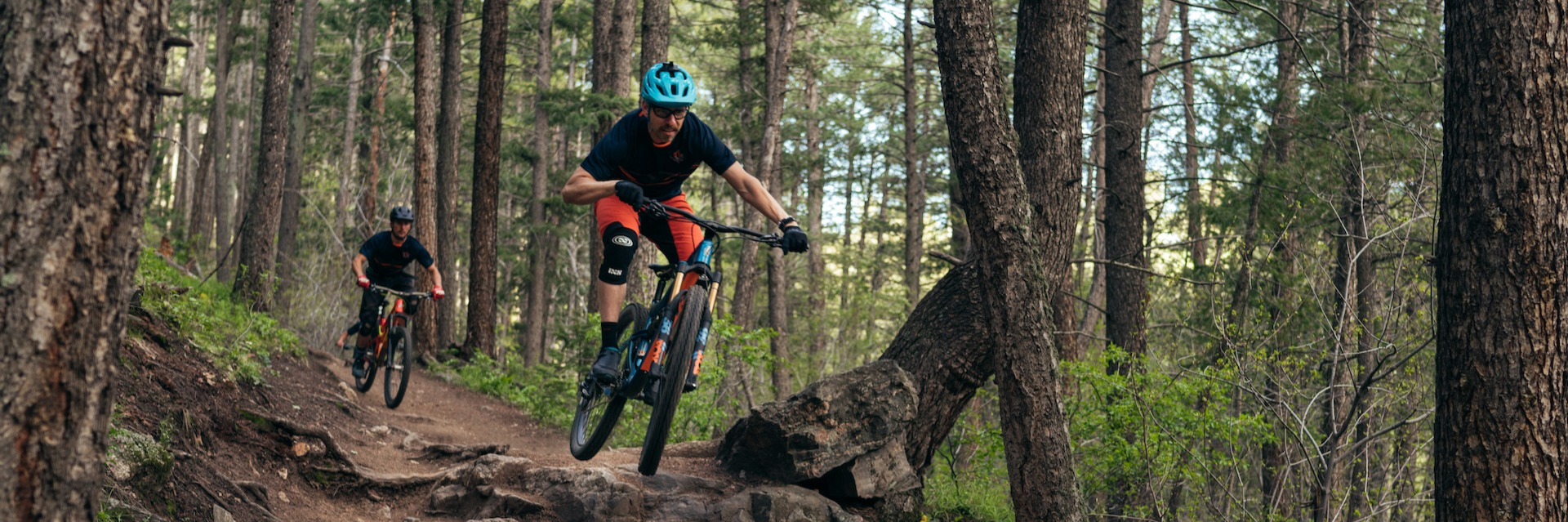 Two men riding mountain bikes down a wooded trail