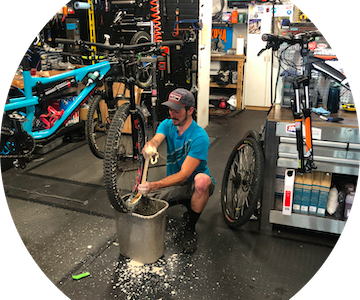 Man in hat fixing handlebar on bicycle at Pedal Pushers Cyclery