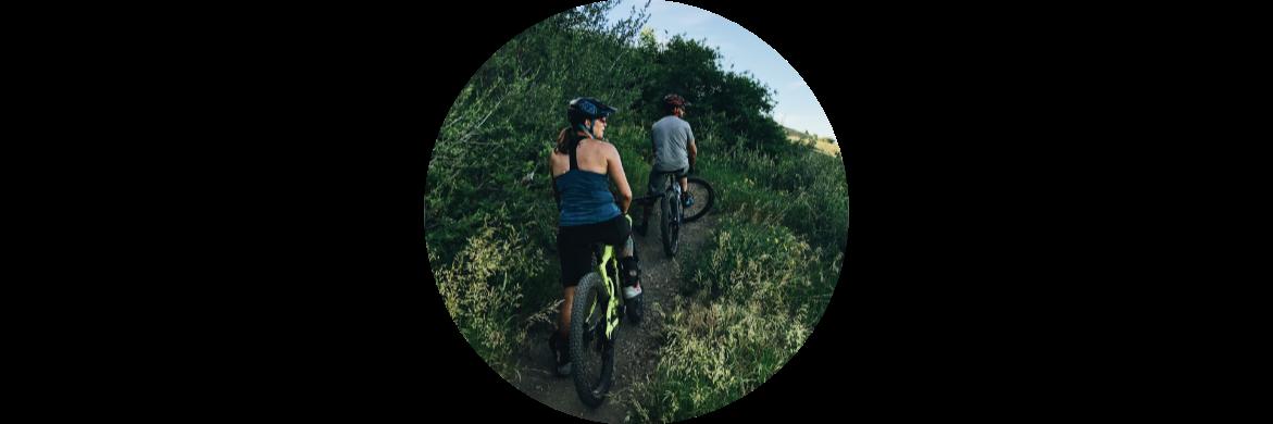 Man and woman mountain riding bikes on trail through green brush