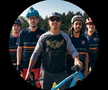 Man in baseball cap and baseball shirt standing in front of four men wearing bike helmets