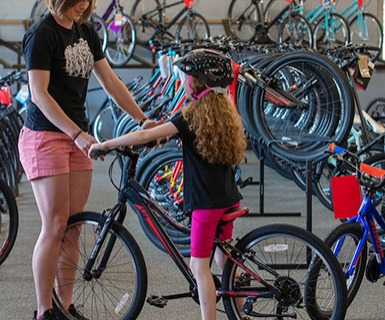 Salesperson helping girl with bike