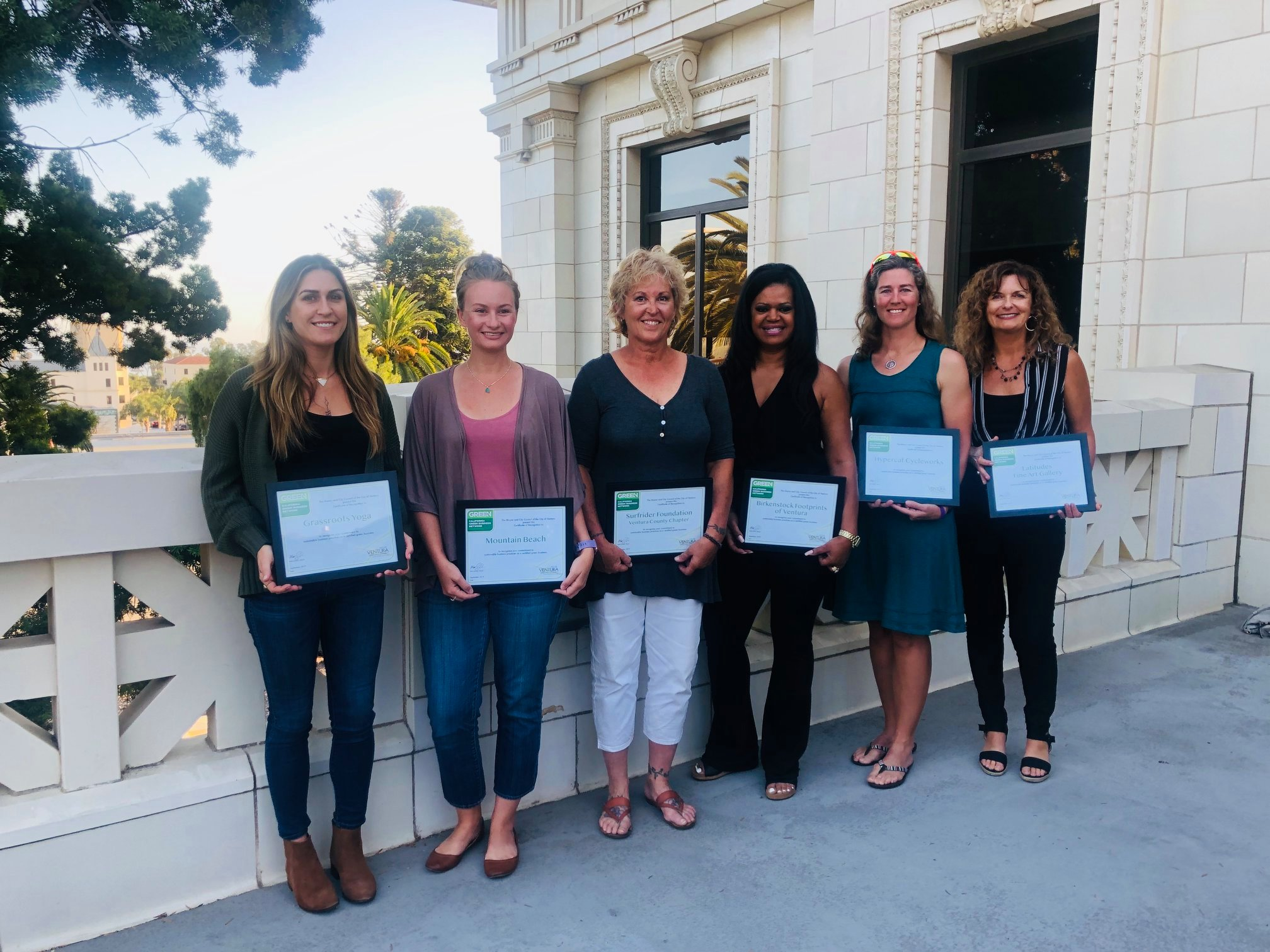 Six business owners holding Green Business certificates outside City Hall in Ventura.