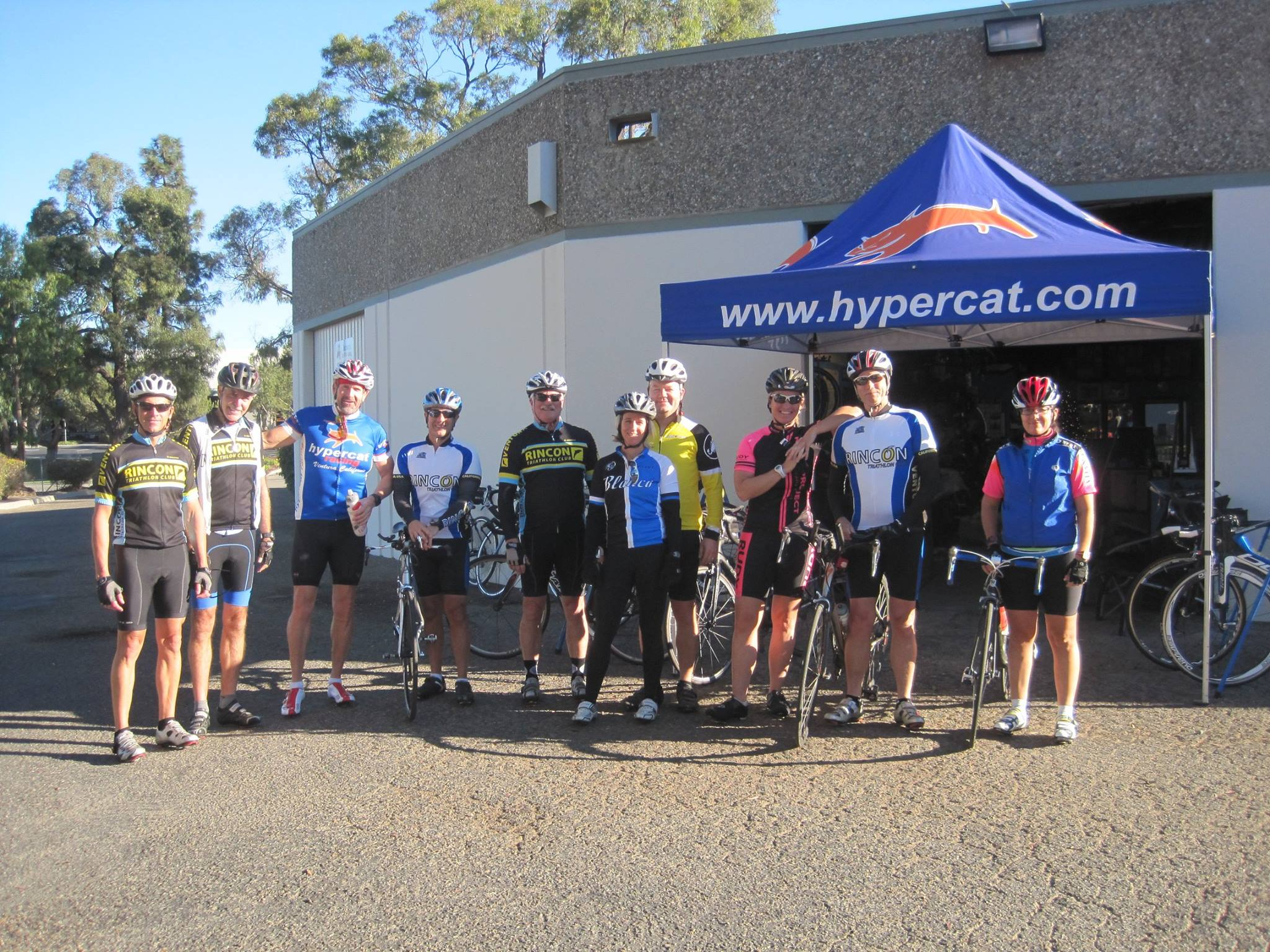 Ten cyclists pose outside Hypercat Cycleworks before a ride