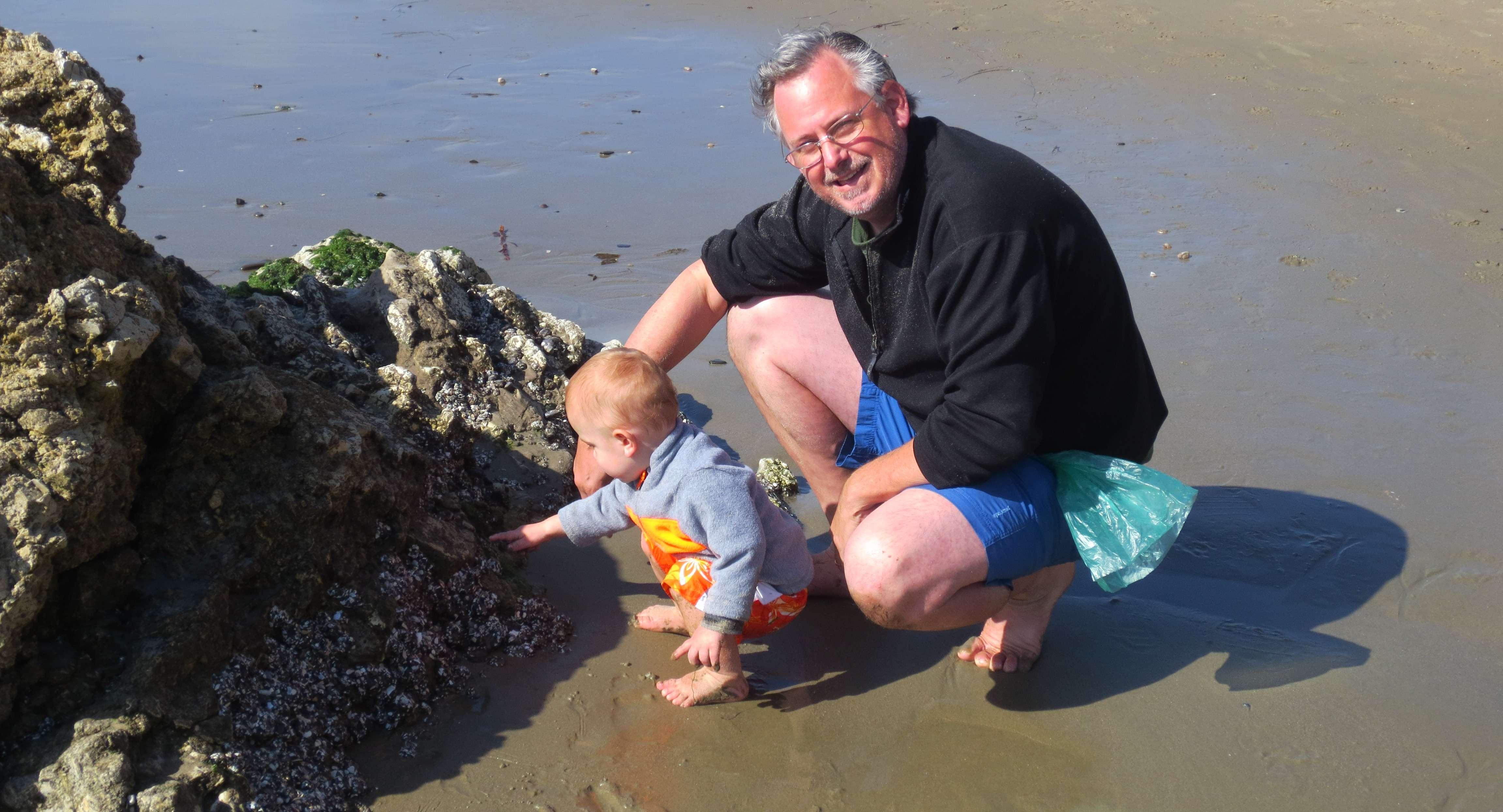 toddler and man near ocean rocks