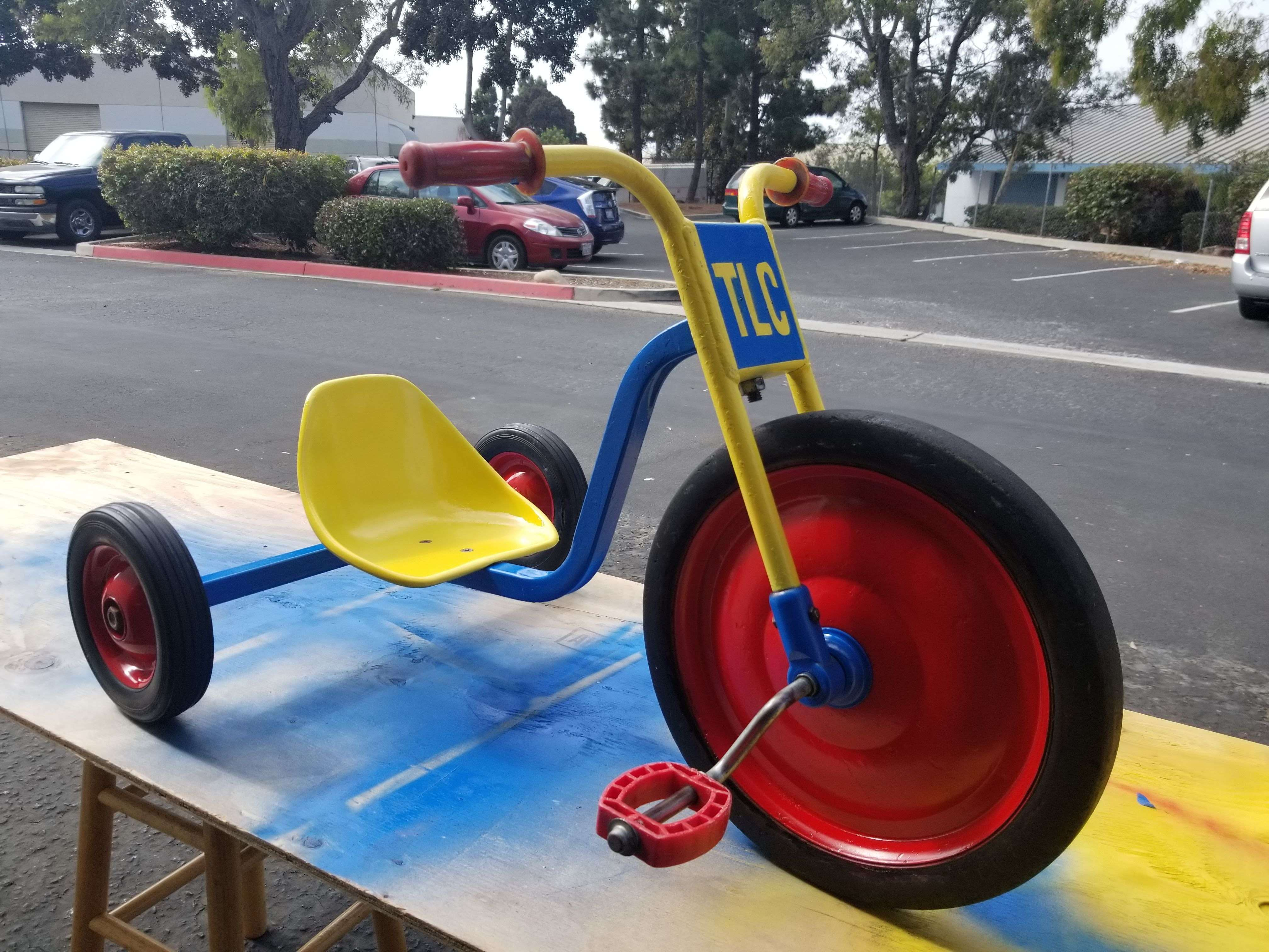 Vintage tricycle in red, yellow and blue with TLC plate