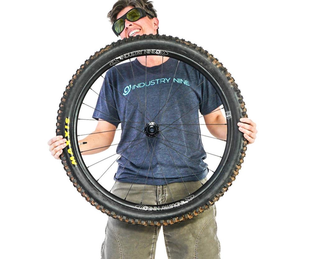 An Industry Nine employee holding a wheel.