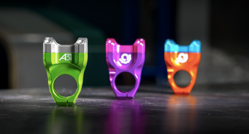 Three Industry Nine stems, one light green with silver, one purple, and one orange with light blue.