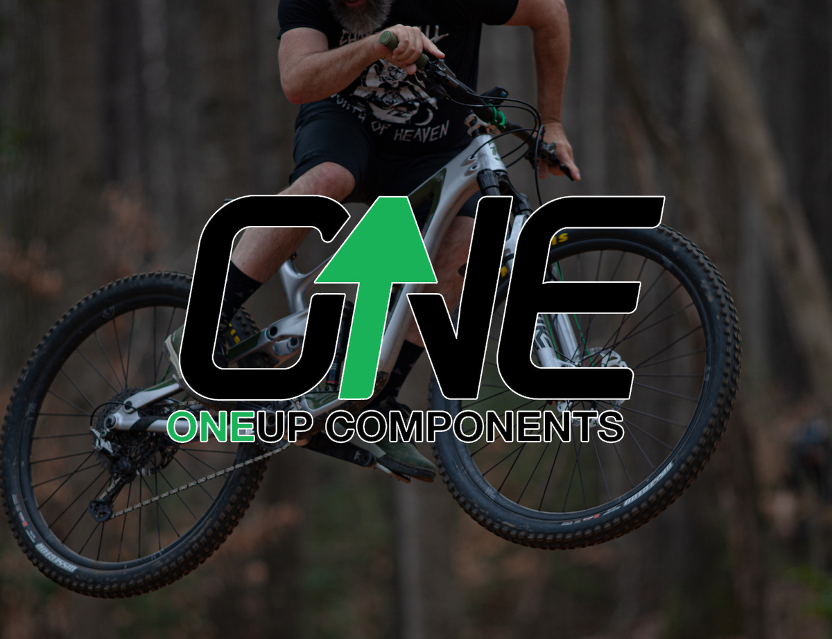 One Up Components Logo on top of a mountain biker jumping through the air.
