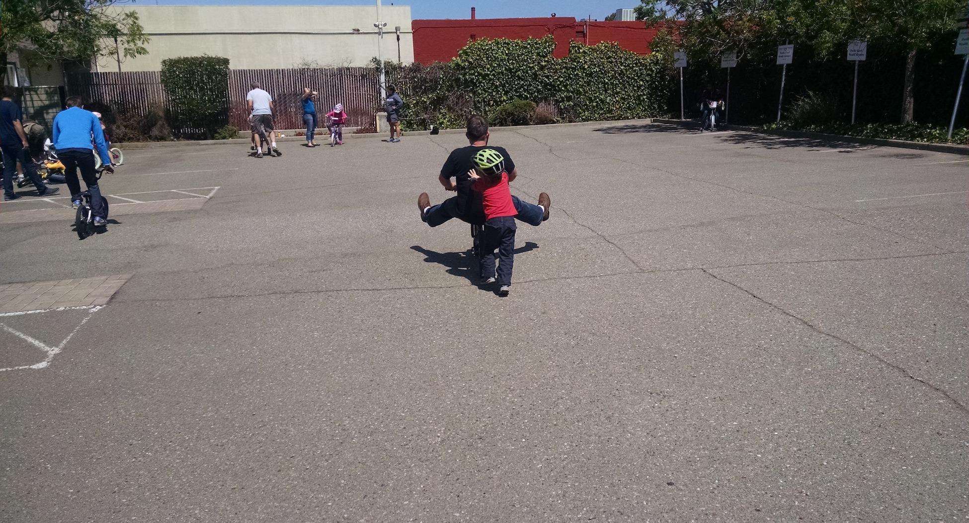 Kid pushing an adult on a kid's bike