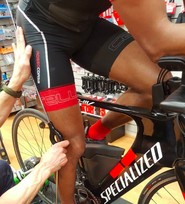 Bike fitter checking a cyclist's knee alignment during bike fit session