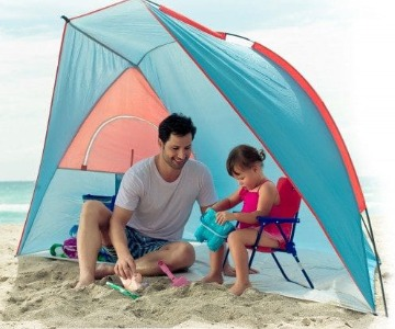 Father and daughter under a beach cabana