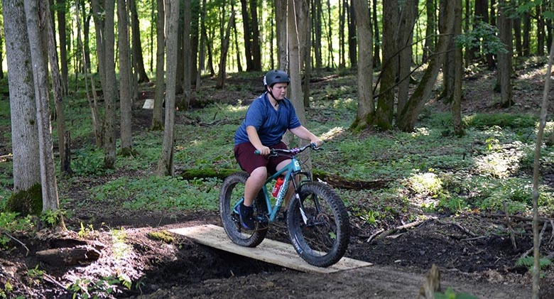 Mountain biker riding a fat bike on trails.