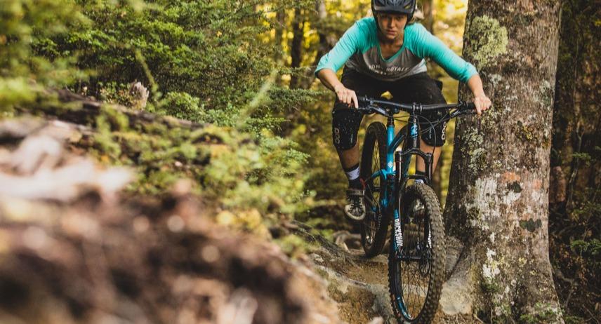 Woman cyclist riding a Kona mountain bike through the woods