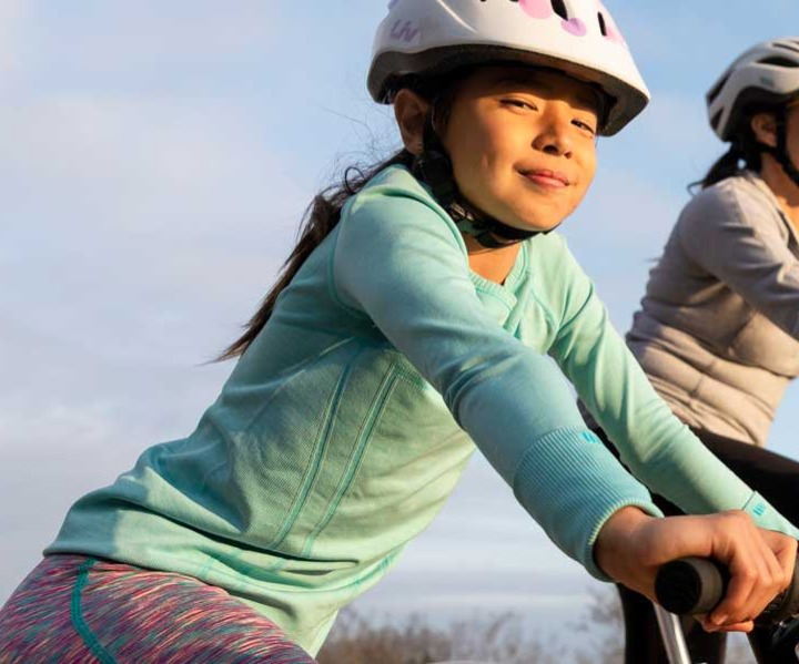Little girl wearing a helmet, riding on her bike