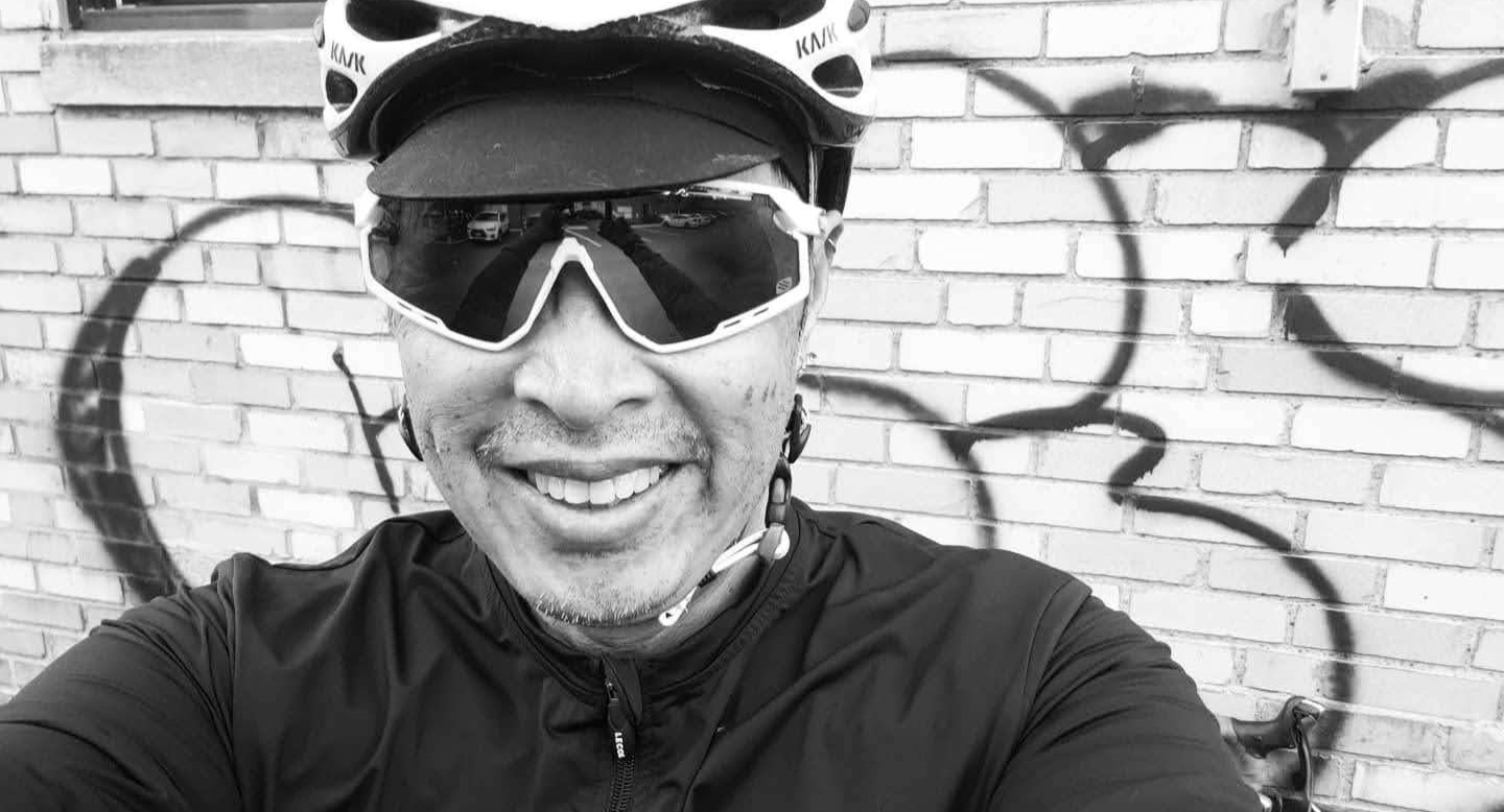 cyclist standing in front of a graffiti wall with bike helmet and performance sunglasses.