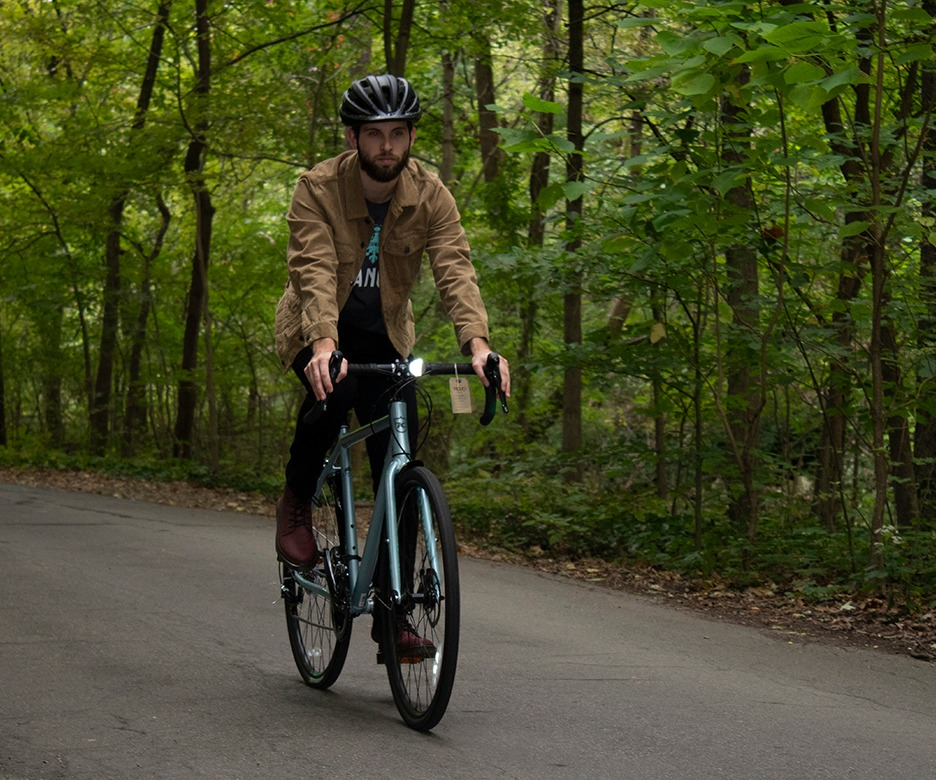 Photograph of cyclist riding on the bike path on a Kona Rove steel bike from Johnny Velo Bikes.