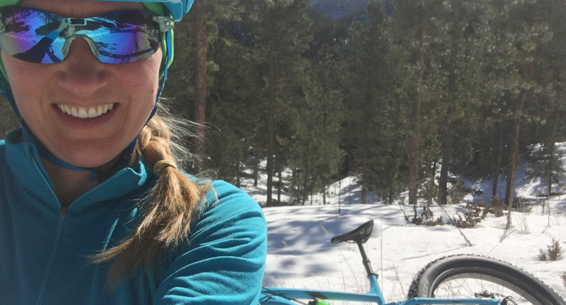 Selfie of a woman mountain biker and her bike in the snow.