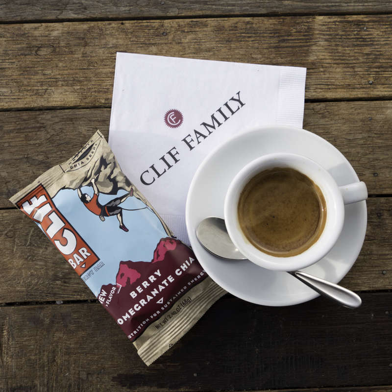 A cup of coffee and a Clif bar sitting on a Clif Family napkin.