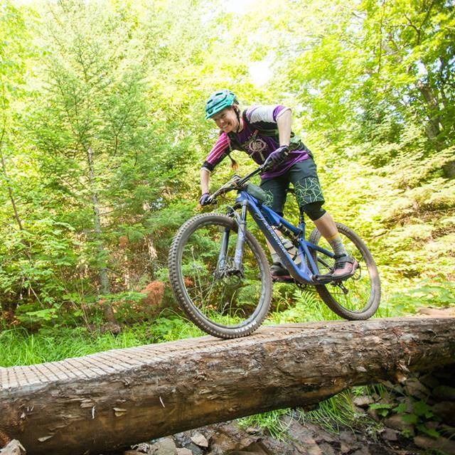 Mountain biker riding across a log bridge