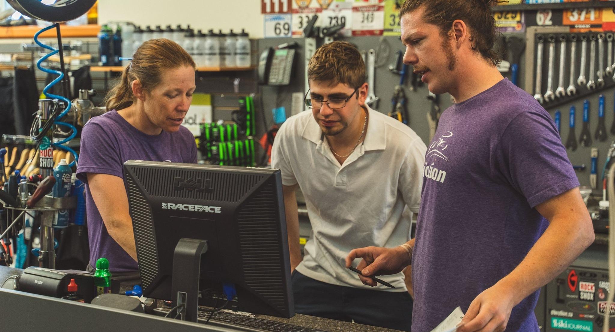 Three employees around a computer