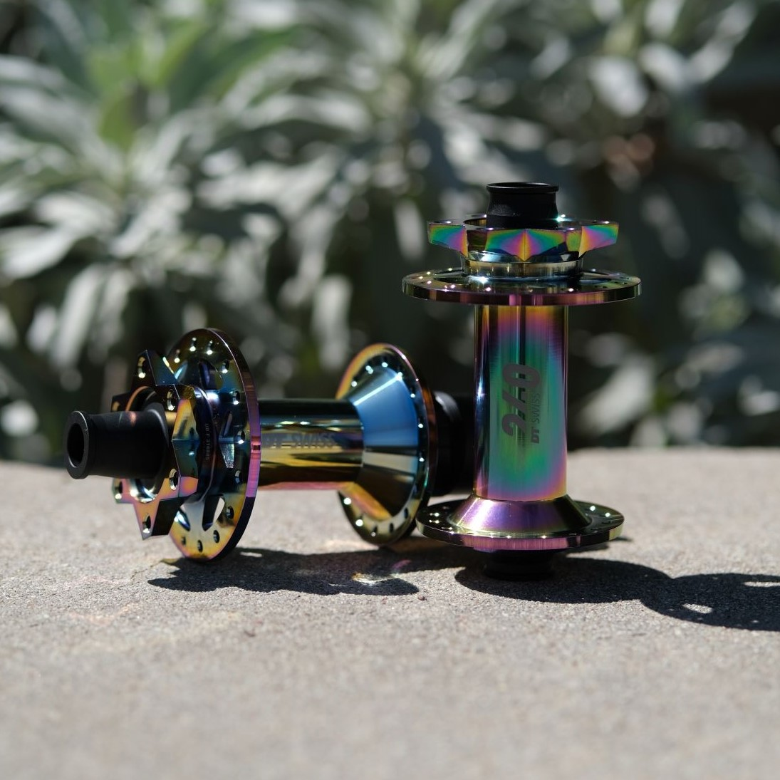 A pair of DT Swiss hubs with an oil-slick finish sit on a bench outside
