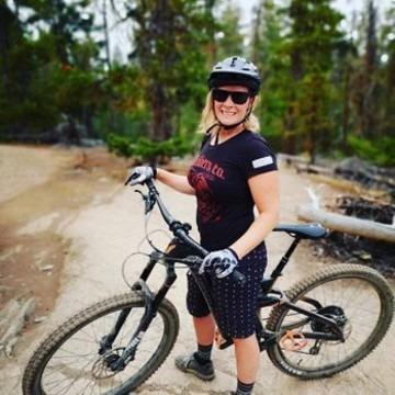 Jessica Blanken standing with full suspension mountain bike