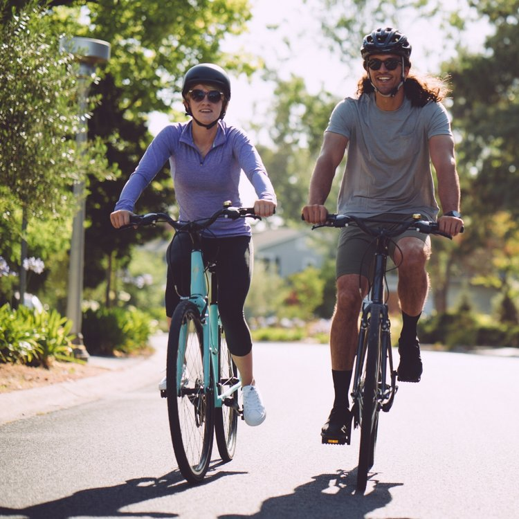 Man and woman riding hybrid comfort bicycles