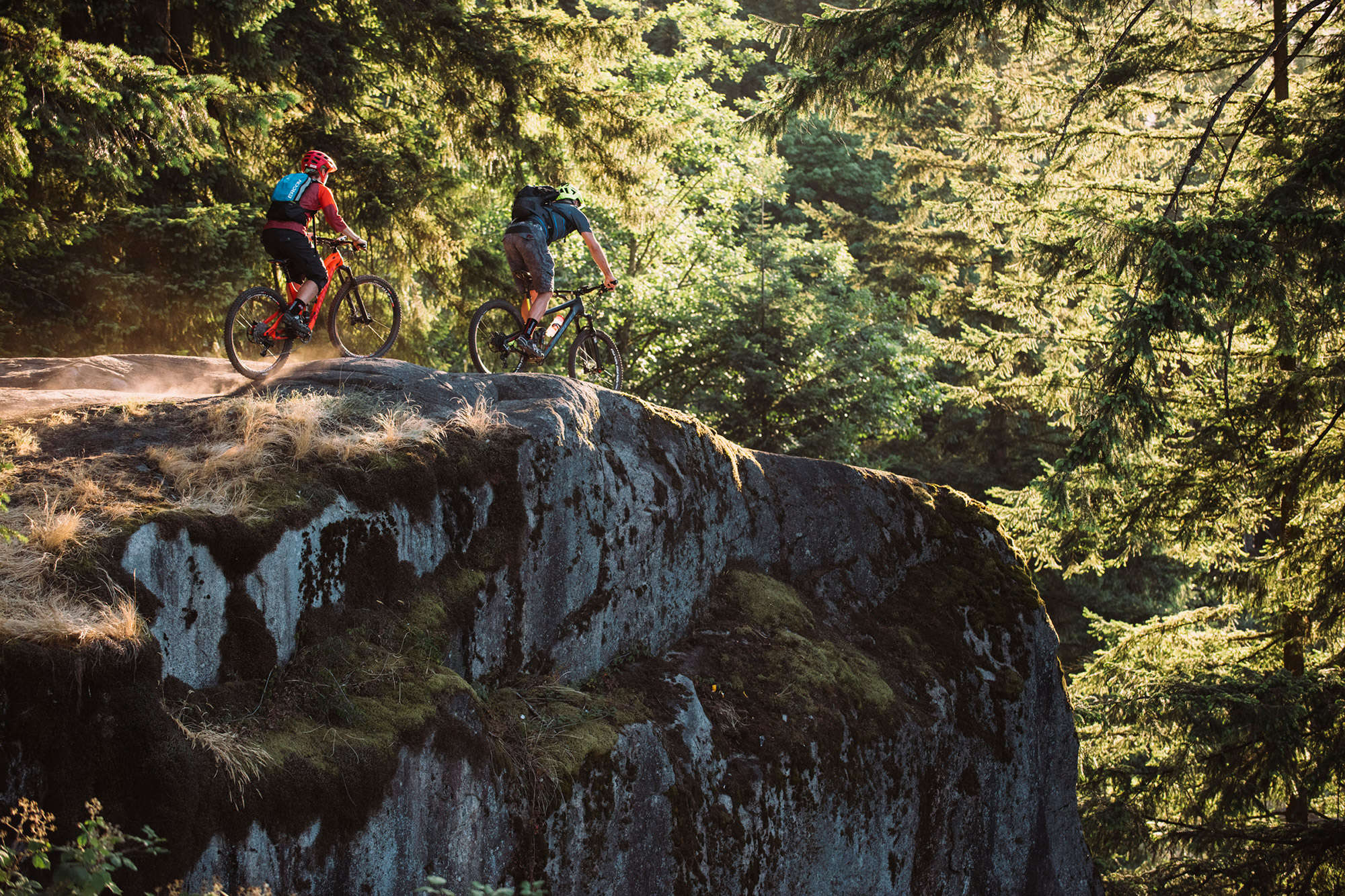 Two Mountain Bikers ride along a cliff.