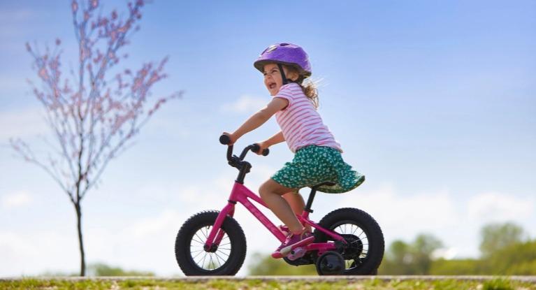 Little girl riding a pink bike.