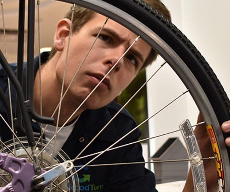 Bike Technician inspecting a wheel